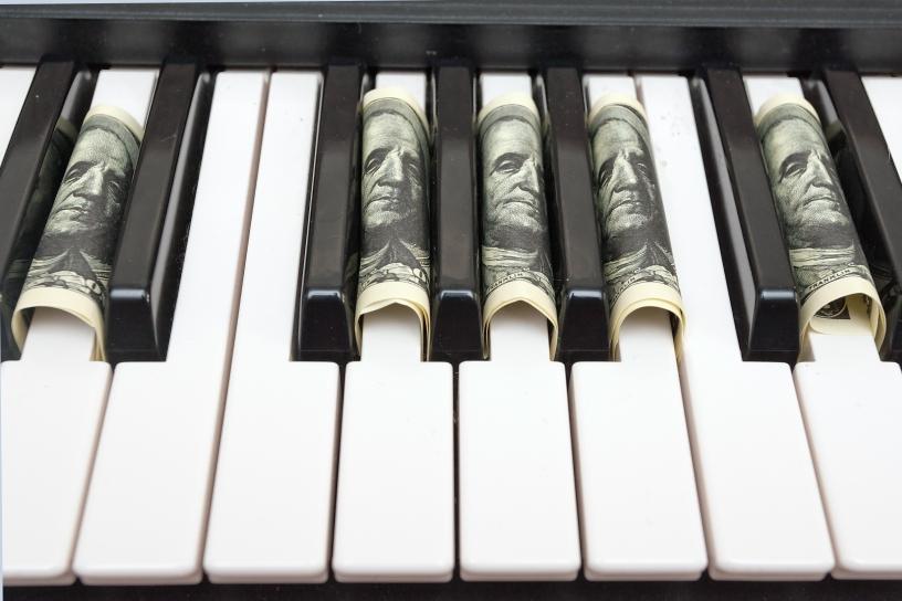 Piano with dollar bills in between keys.