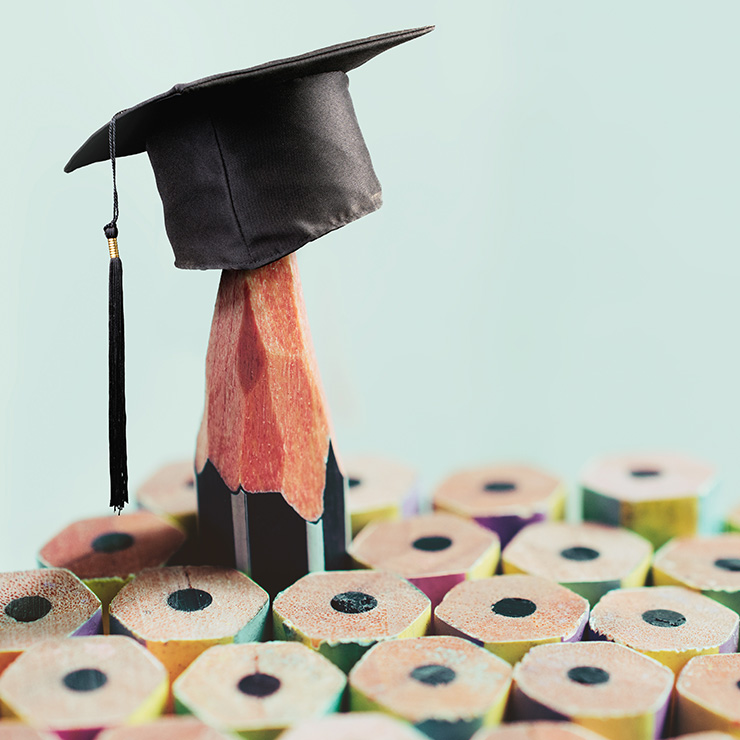 Group of pencils wearing graduation cap.
